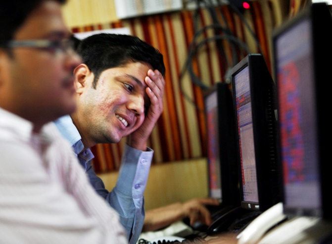 A dealer reacts while trading at a stock brokerage firm in Kolkata.