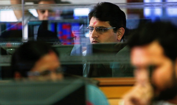 A broker monitors share prices while trading at a brokerage firm in Mumbai.