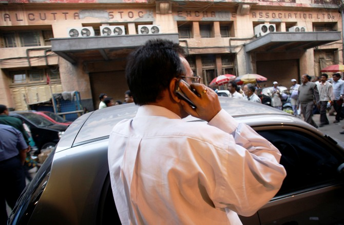 An investor monitors stock news through a mobile phone in front of the Kolkata Stock Exchange building.