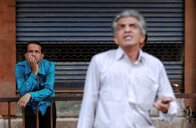 People look at a screen displaying the Sensex on the facade of the Bombay Stock Exchange building.