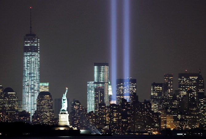 The Tribute in Light is illuminated next to the Statue of Liberty (C) and One World Trade Center (L) during events marking the 12th anniversary of the 9/11 attacks on the World Trade Center in New York, September 10, 2013.