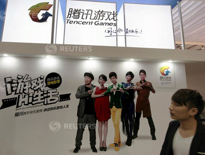 A man walks past in front of a booth of Tencent Games during the 10th China International Digital Content Expo in Beijing.