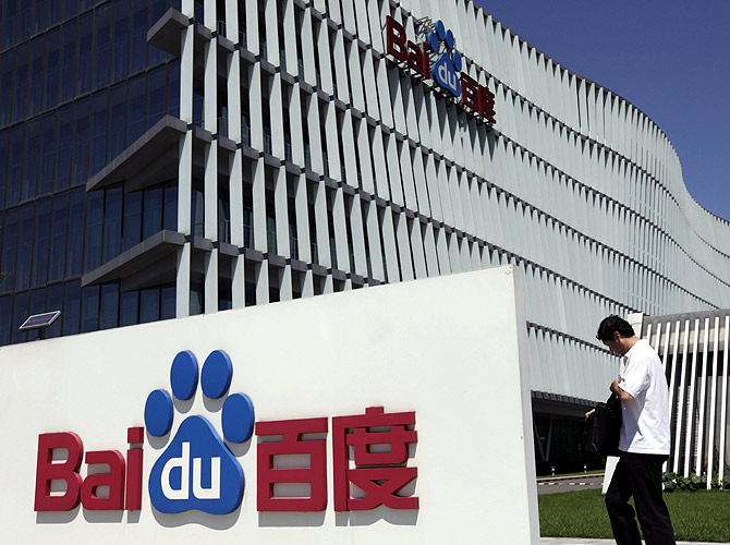 An employee walks past the Baidu company signage outside its headquarters in Beijing.