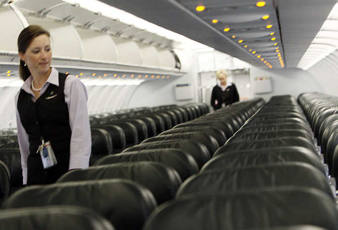 Frontier Airlines's flight attendant Cheryl Jacquot checks seats for safety cards before a trip to Washington, DC, at the Denver Airport, Colorado, United States.