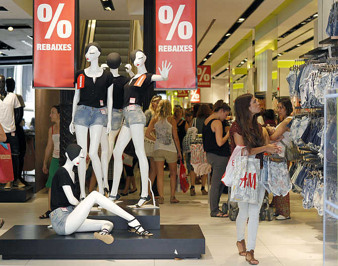 A woman looks at clothes inside a Bershka's shop in central Barcelona, Spain.