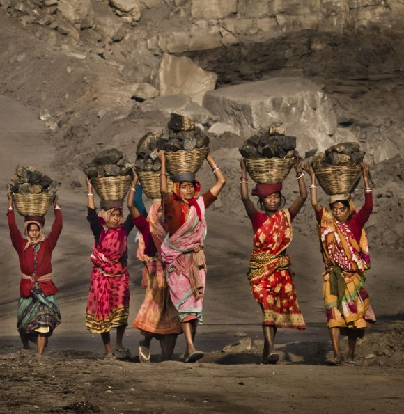 Local villagers carry coal after having scavenged it from an open-cast coal mine.