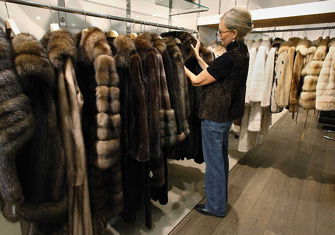 Saleswoman Annette Bourbon arranges a display of mink and sable coats at a fur salon in downtown Copenhagen, Denmark.
