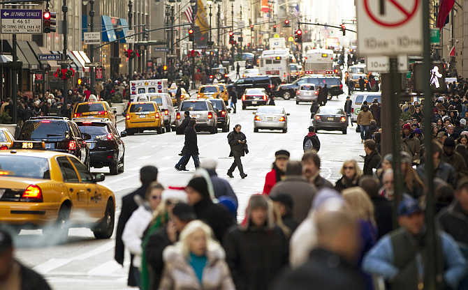 Pedestrians walk across 5th Avenue while shopping in New York City, United States.