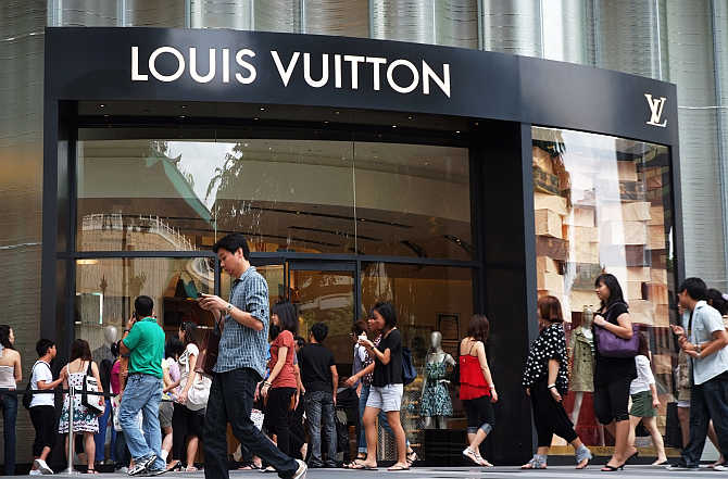 Shoppers walk past a Louis Vuitton store at the Ion Orchard shopping mall in central Singapore.