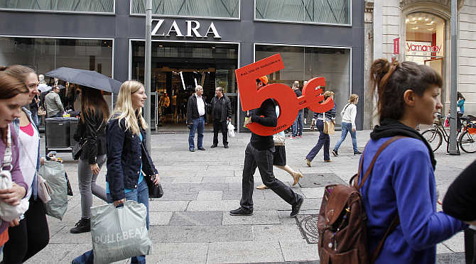A man holds a foam cutout of five euros, which is an advertisement for a shop, as he walks in central Barcelona, Spain.