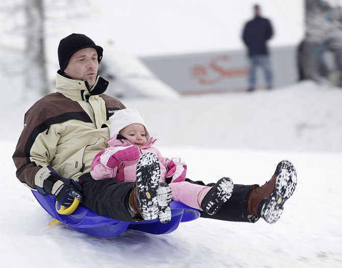 People enjoy sledging in the snow at the Chalet-a-Gobet in Lausanne, Switzerland.