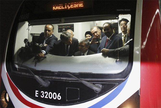 Japanese Prime Minister Shinzo Abe (R), Turkey's Prime Minister Tayyip Erdogan (3rd R) and President of Somalia Hassan Sheikh Mohamud (2nd R) stand around Turkey's President Abdullah Gul (seated) as he rides the ceremonial service of a train during the opening ceremony of Marmaray.