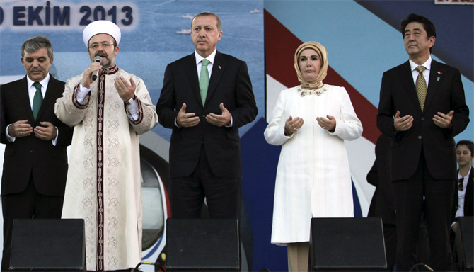 Japanese Prime Minister Shinzo Abe (R), Turkey's President Abdullah Gul , Prime Minister Tayyip Erdogan (C), his wife Emine Erdogan pray with Head of Turkey's Religious Affairs Directorate Mehmet Gormez during the opening ceremony of Marmaray.