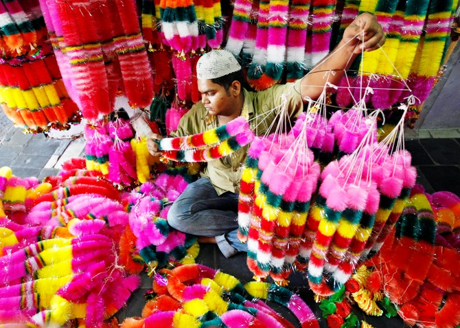 A vendor arranges artificial garlands for sale inside his shop ahead of Diwali in Ahmedabad.