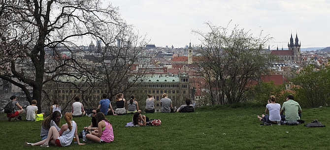 People enjoy the view during a warm spring day at Letna plain above central Prague, Czech Republic.