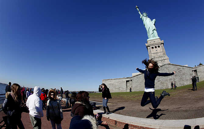 A visitor leaps beneath the Statue of Liberty at Liberty Island in New York, United States.