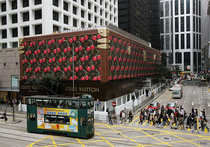 A tram passes a giant Louis Vuitton steamer trunk wrapping the exterior of a shopping mall at Hong Kong's Central Business District.