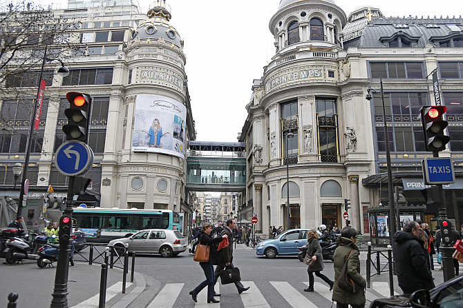 People walk past the Printemps department store in Paris, France.