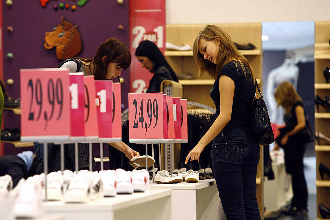 Women look at shoes in a shopping centre in Riga, Latvia.