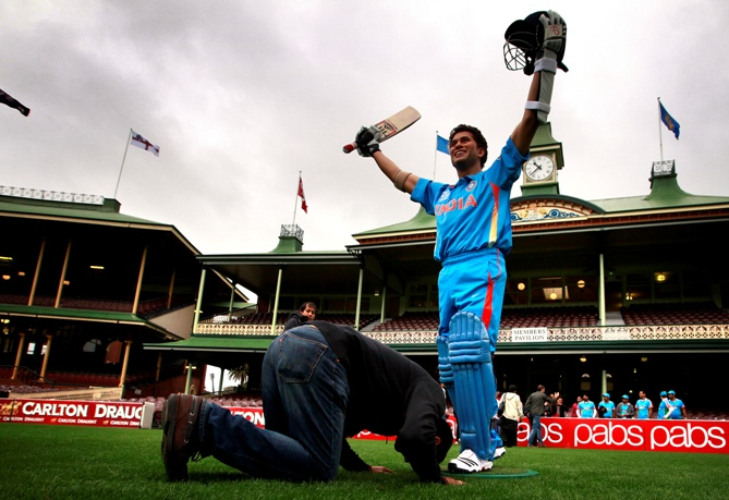 An Indian cricket supporter kneels in front of a wax figure of Sachin Tendulkar during a promotional event at the Sydney Cricket Ground April 20, 2013.