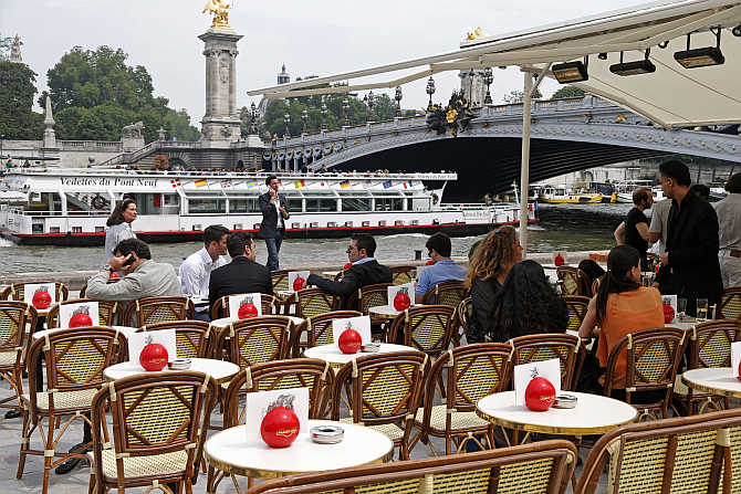 People sit at a terrace cafe near the Alexandre III bridge between the Orsay Museum and Alma Bridge on the left bank of the River Seine in Paris, France.