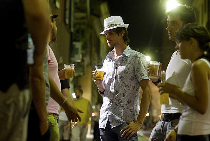 Young Italians drink beer in downtown Milan, Italy.