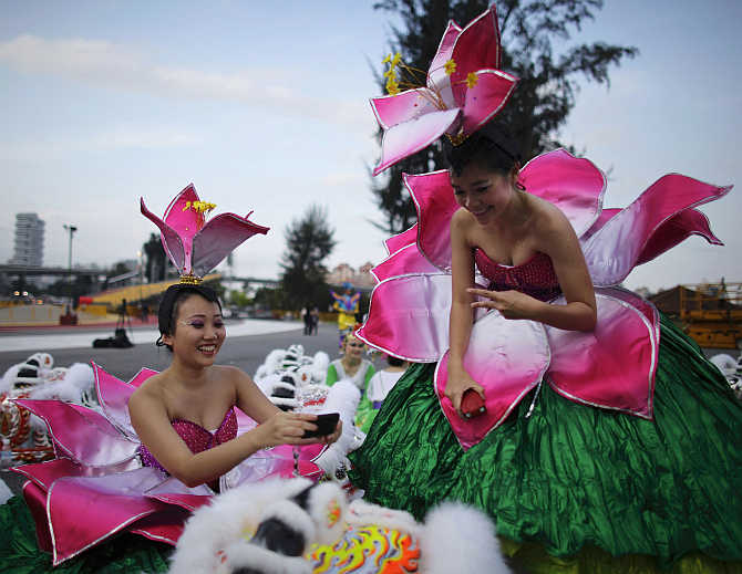 A performer poses in front of a Chinese lion head as her friend takes photo before the dress rehearsal for the Chingay parade in Singapore.