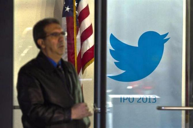 A man walks past a Twitter banner while leaving JP Morgan headquarters, before Twitter's IPO in New York October 25, 2013.