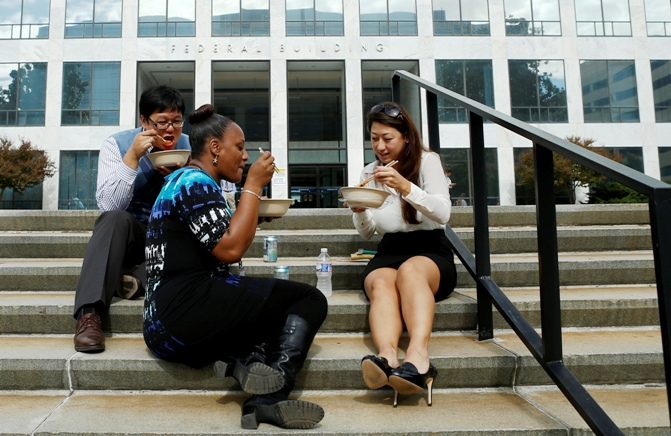Workers have lunch on the steps of a federal in Washington October 17, 2013.