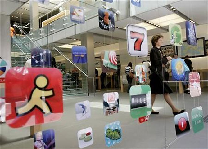 A woman walks past icons for Apple applications at the company's retail store.