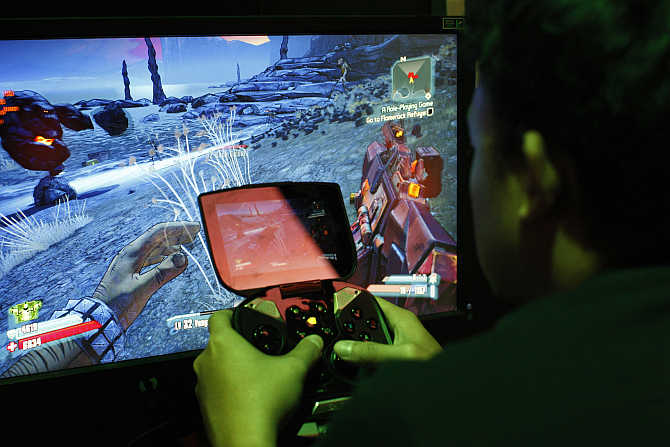 A man tries a game at the Nvidia Shield PC Game Streaming exhibit at E3, the Electronic Entertainment Expo, in Los Angeles, California.