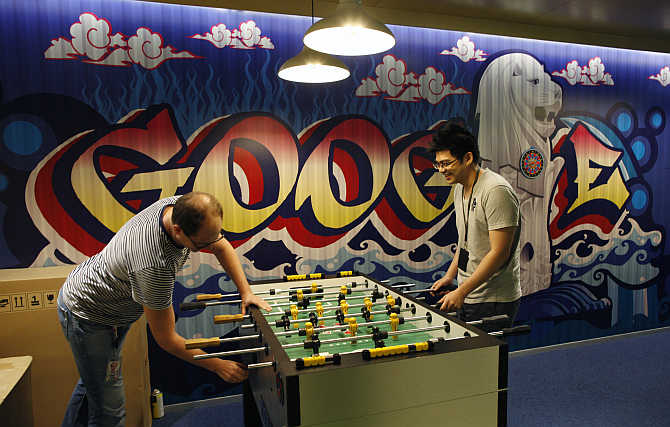 Google employees play table soccer at a recreational area of their Singapore office.