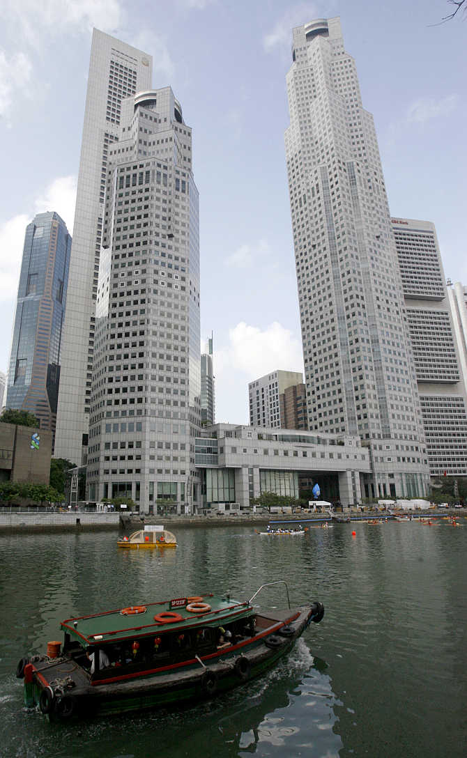 A boat sails past office buildings in Singapore.