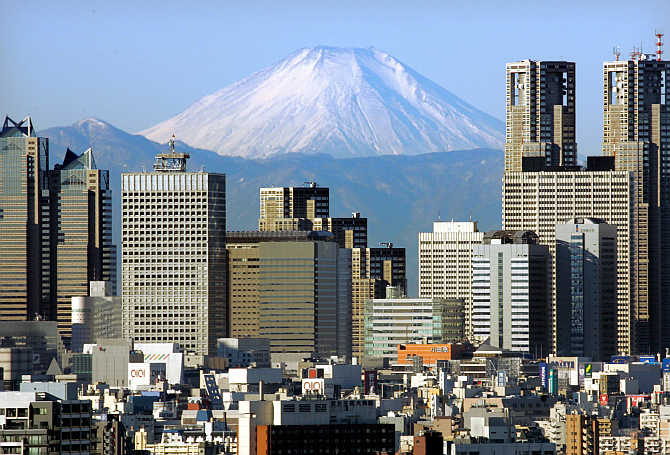 Mt Fuji, covered with snow, is seen through Shinjuku skyscrapers in Tokyo, Japan.