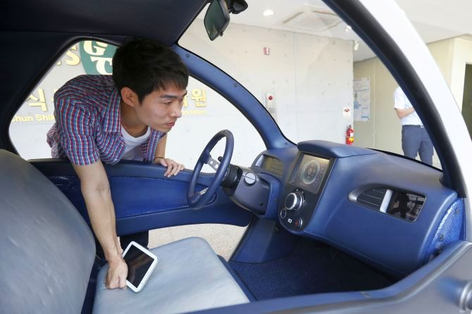 A researcher looks at the interior of Armadillo-T, a foldable electric vehicle, at the Korea Advanced Institute of Science and Technology (KAIST) in Daejeon, south of Seoul.