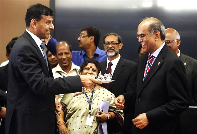 Raghuram Rajan (L), newly appointed governor of Reserve Bank of India (RBI), offers sweets to the outgoing governor Duvvuri Subbarao.