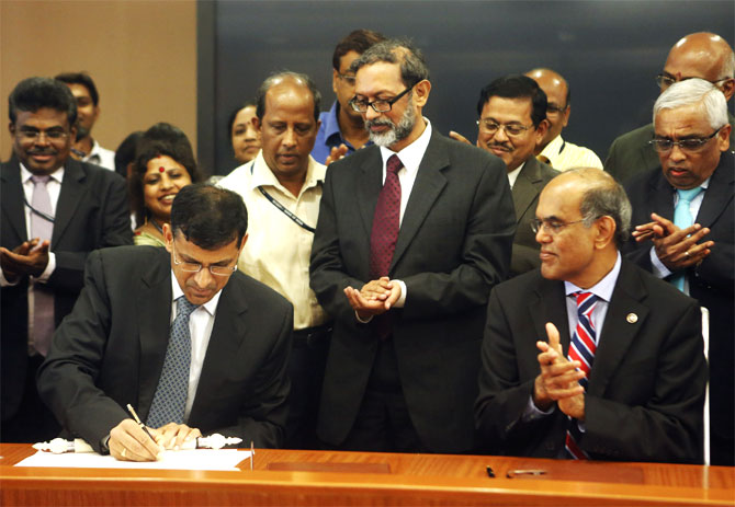 Raghuram Rajan (L), newly appointed governor of Reserve Bank of India (RBI), signs papers during the taking over ceremony at the bank's headquarters in Mumbai.