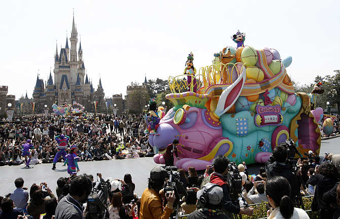 Mickey Mouse, top, performs atop a float at Tokyo Disneyland in Urayasu, east of Tokyo, Japan.