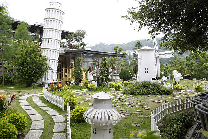 Visitors walk in a yard filled with paper structures at Carton King Creativity Park in Taichung, central Taiwan.