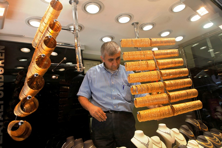 An employee arranges gold bangles at a jewellery shop.