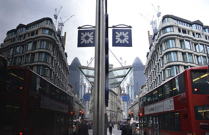 A logo from a Royal Bank of Scotland branch is reflected in a window in the City of London.