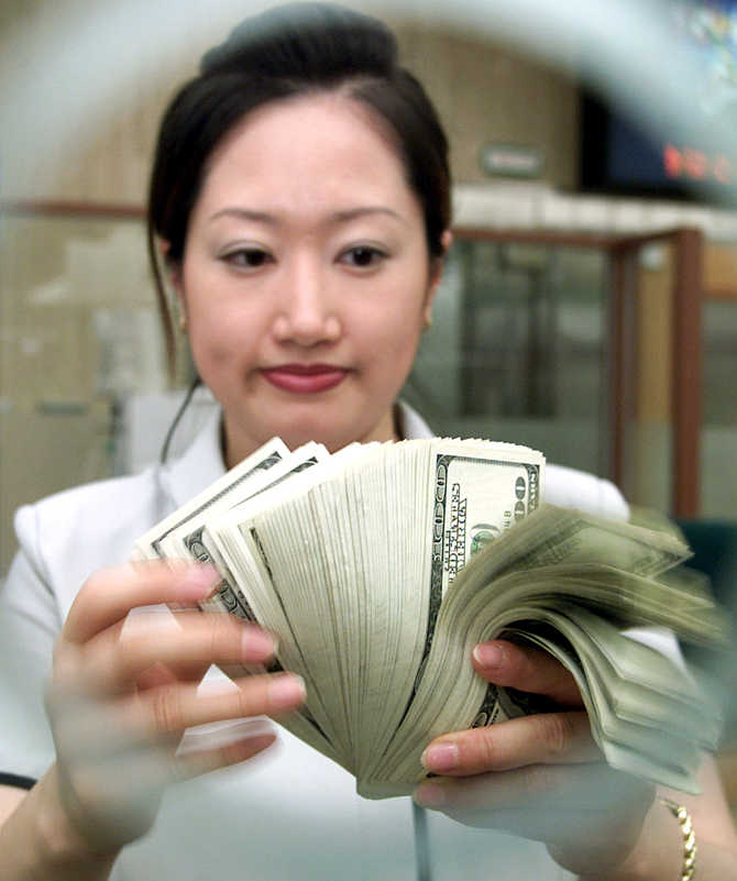 A bank clerk counts dollar notes in Seoul, South Korea.