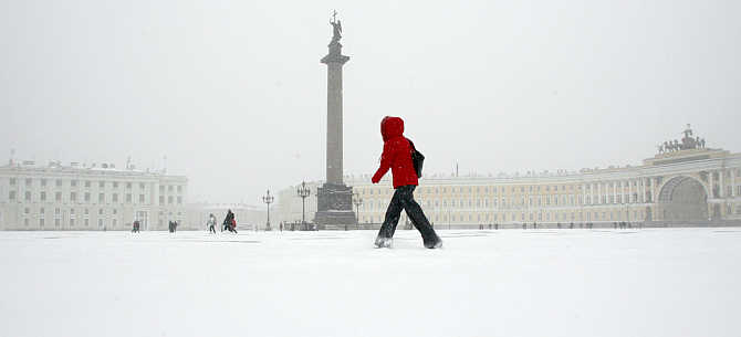 A woman crosses Palace Square in central St Petersburg during a snowstorm, Russia.