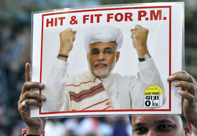 A supporter of India's main opposition Bharatiya Janata Party (BJP) holds a poster featuring Narendra Modi during a jubilation ceremony outside the party office in the western Indian city of Ahmedabad.