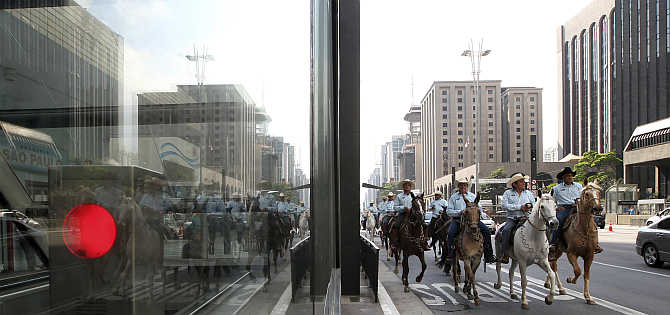 People ride horses along a main avenue in the financial centre of Sao Paulo during World Car Free, in Brazil.