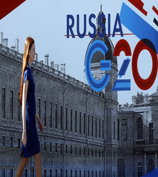 An employee passes by a sign at the main press centre of the G20 summit in Strelna near St. Petersburg.