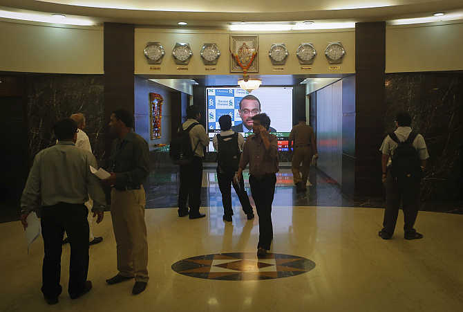 Employees stand in a lobby as they wait for the elevator inside Bombay Stock Exchange building in Mumbai.