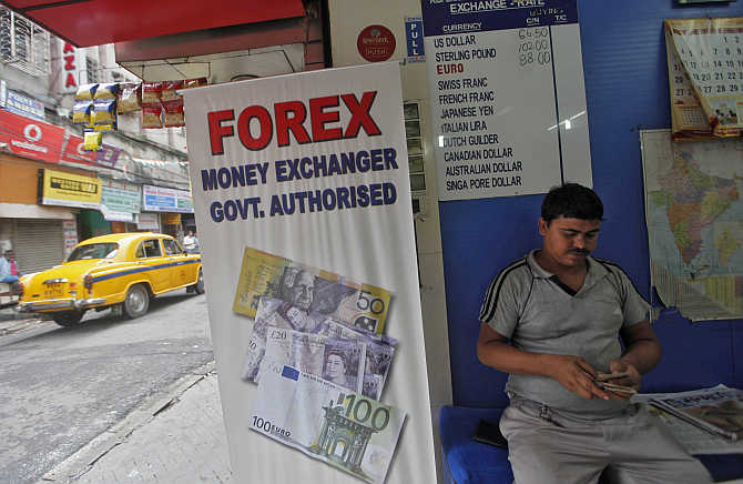 A customer counts currency inside a currency exchange shop in Kolkata.