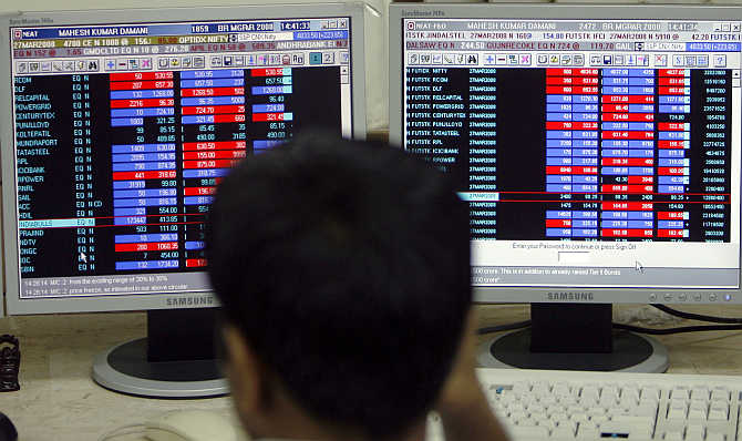 A broker monitors index numbers on his computer terminals at a stock brokerage firm in Mumbai.