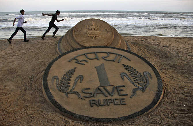 Boys run near a sand sculpture of the Rupee created by artist Sudarshan Pattnaik at golden sea beach in Puri, Orissa.